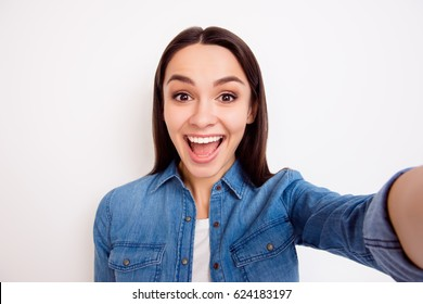 Young pretty cheerful girl in jeans shirt taking  self-portrait on white background