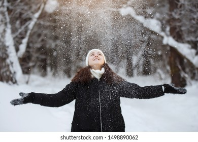 Young, pretty, cheerful long-haired woman in a black jacket and white hat with a pompon smiles, throws snowflakes in the winter outside in a snowy forest.