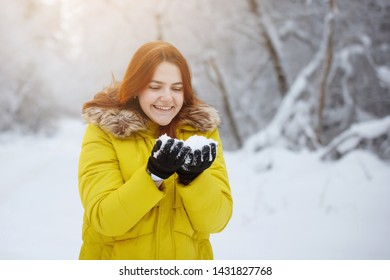 Young, pretty, cheerful red-haired long-haired woman in a mustard jacket smiles and rejoices, blows snowflakes from her hands in the winter outside in a snowy forest.