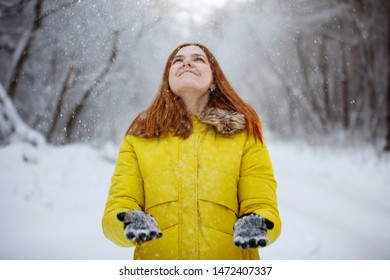 Young, pretty, cheerful red-haired long-haired woman in a mustard jacket is smiling, throwing snowflakes from her hands in the winter outside in a snowy forest.