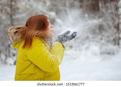 Young, pretty, cheerful red-haired long-haired woman in a mustard jacket smiles, blows snowflakes from her hands in the winter outside in a snowy forest.