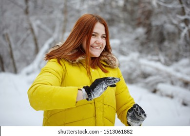 Young, pretty, cheerful red-haired long-haired woman in a mustard jacket smiles and rejoices, shakes off snowflakes from her hands in the winter outside in a snowy forest.