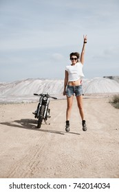 Young pretty cheerful woman jumping with raised hand. Girl biker with perfect fit slim tamed body and custom cafe racer motorbike on the desert. Outdoor lifestyle portrait