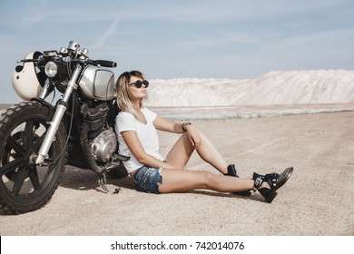 Young pretty cheerful woman sitting on ground next to custom cafe racer motorbike on the desert. Girl biker with perfect fit slim tamed body and long hairs. Outdoor lifestyle portrait