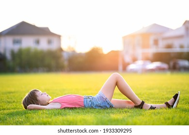 Young pretty child girl relaxing lying down on green grass on warm summer evening.