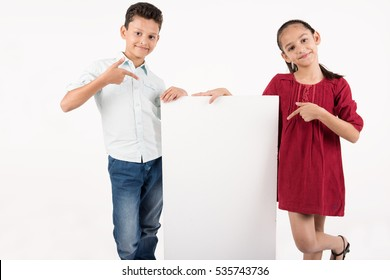 young pretty children standing near a white boar on white background