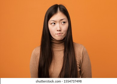 Young pretty chinese woman confused, feels doubtful and unsure.