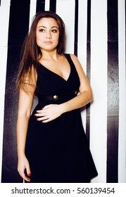 young pretty cool fat brunette woman with long hair fashion dressed in little black dress happy smiling, lifestyle people concept