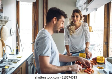 Young pretty couple cooking together dinner at kitchen and talking.
