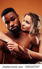 Young pretty couple diverse races together posing sensitive on brown background, lifestyle people concept