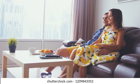 Young pretty couple in love watching TV at living room in apartment by the panoramic window.
