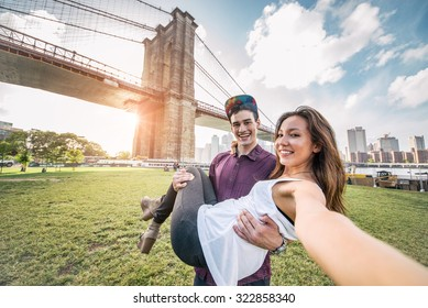 Young pretty couple taking a selfie at Brooklyn Bridge, New York - Boyfriend holding his girlfriend and having fun while sightseeing