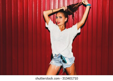 Young  pretty crazy  hipster woman in trendy autumn clothes have fun and doing grimaces  near red  background  urban style  on  night party.  Bright flash ,  contrast color .