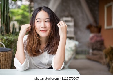 Young pretty, cute and beautiful business woman wearing white shirt looking camera with smile emotion in the cafe garden