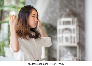 Young pretty, cute and beautiful business woman wearing white shirt looking or checking her self at mirror in the cafe garden