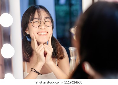 Young pretty, cute and beautiful woman make up her self in front of the mirror at the dressing table or vanity with smile emotion
