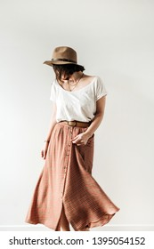 Young pretty dancing woman in long skirt, hat, white blouse on white background. Fashion lifestyle trendy stylish clothes look.