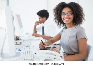Young pretty designer smiling at camera at her desk in her office