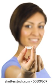 Young, pretty ethnic woman holds a white pill.