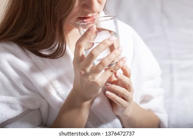 Young pretty european woman holding a glass and drink pure water sitting on the sofa. Cleansing the body of toxins. Healthy skin. Oily skin. Close up partrait of beautiful woman in bathrobe.