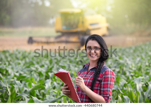 Young pretty farmer girl writing notes on field while combine harvester working in background
