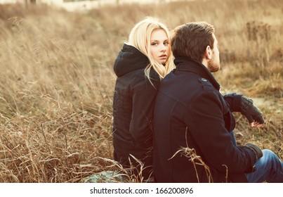 Young pretty fashion sensual couple in love sitting in winter cold field