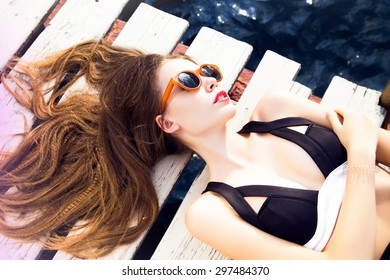 a3bca9e85f8 Young pretty fashion woman body posing in summer in pool with clear water  lying on mattress