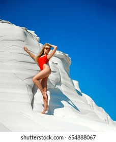 Young pretty fashion woman standing posing on white rocks near sea shore beach resort in red sexy body swimsuit and round sunglusses on blue sky background