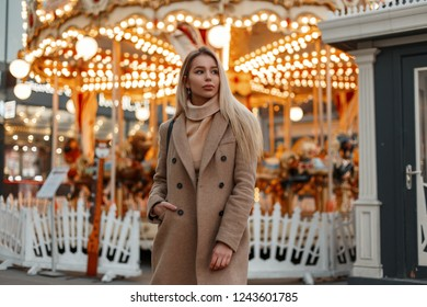 Young pretty fashion woman in a stylish autumn coat and vintage knitted sweater walks in an amusement park on the background of a carousel decorated with a garland. Elegant girl. Festive atmosphere