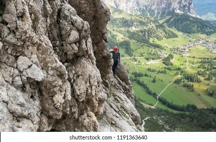 young pretty female mountain climber on a Via Ferrata in the Dolomites in Alta Badia