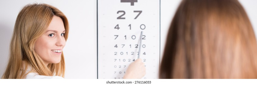 Young pretty female ophthalmic optician and snellen chart