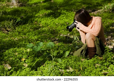 Young pretty female photographer in nature
