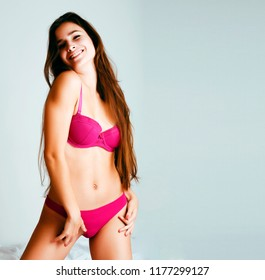 young pretty female in pink underwear in her bed smiling confide