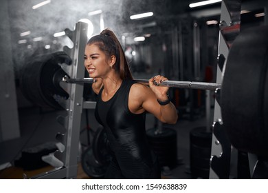 Young pretty female powerlifter trying to lift heavy weight, standing near metal bar, holding tightly professional barbell, looking away with strong, showing teeth, demonstrates effort, portrait