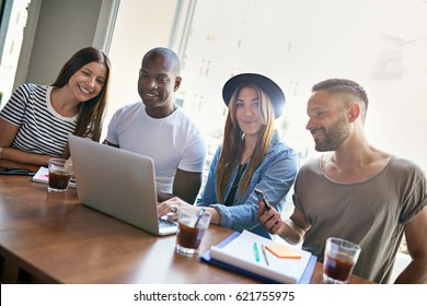 Young pretty female sitting with three co-workers at desk with laptop and looking at camera.