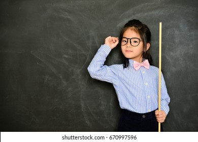 young pretty female tutor using stick teaching study class and standing in chalk blackboard background. back to school education concept.