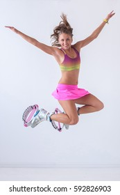 Young and pretty fitness instructor makes exercise using Kangoo boots