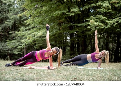 Young pretty fitness sporty two woman doing joga outdoor