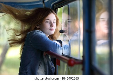 Young pretty freckled girl enjoying trip at public transport, the wind blowing her hair through an open window