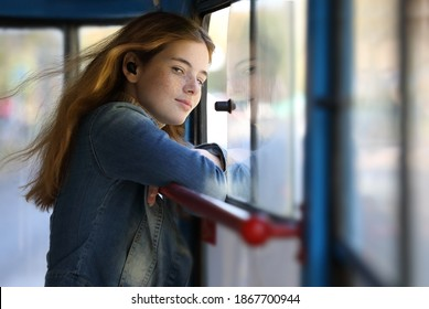 Young pretty freckled girl enjoying trip at public transport on a summer day, the wind blowing her hair through an open window