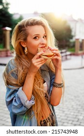 Young pretty funny blond girl eats hamburger fast food sandwich on the street