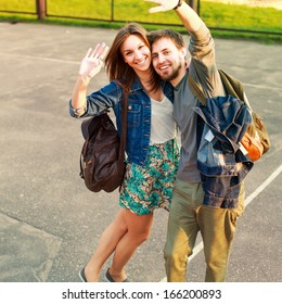 Young pretty funny happy smiling couple posing outdoor on school yard and saying hello and having fun together in love
