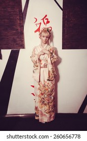 young pretty geisha in kimono with flower and decoration