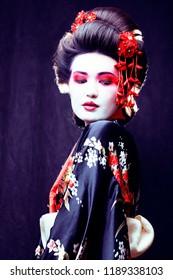 young pretty geisha in kimono with sakura and decoration on blac