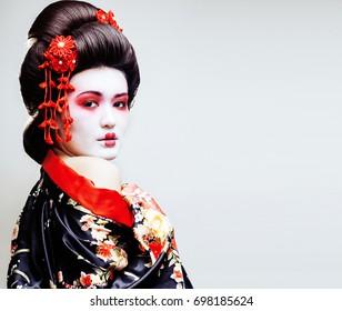 young pretty geisha in kimono with sakura and red decoration des