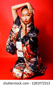 young pretty geisha on red background posing in kimono, oriental