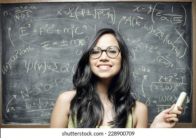 A young pretty genius girl over equations on blackboard