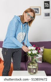 Young pretty girl arranges flowers in the home