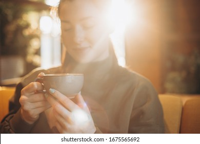 young pretty girl with a big mug of sweet coffee sits on a chair in her favorite cafe and drinks her daily morning coffee and talks with a girlfriend
