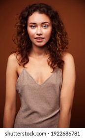 young pretty girl with blond curly hair posing cheerful on brown background, lifestyle people concept